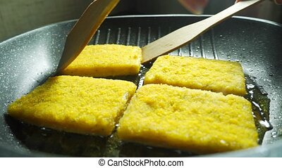 Turning over frying crumbed fish fillets with spatulas, close up video