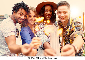 Multi-ethnic millenial group of friendsfolding sparklers on...