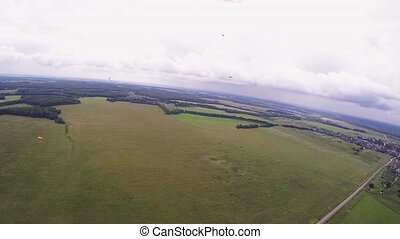 Skydiver fly on parachute above green fields and forest. High altitude. Summer.