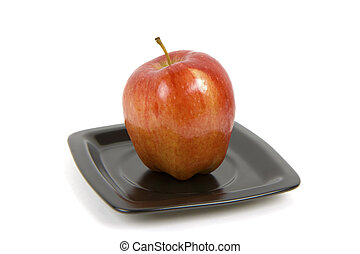 red apple on the black plate