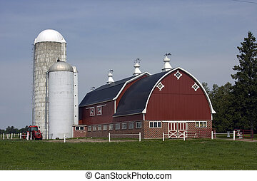 red barn and farm - red barn with silos and tractor on a...