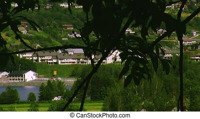 Panoramic view city at coast of river. Hilly country. Little white houses. Lot greenery. Summer day
