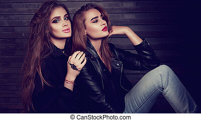 Glamour makeup two women with long hair style sitting on street wall background in dark. Fashion color portrait