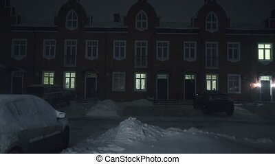 Snowfall in townhouse residential area at night clip