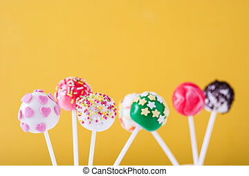 Cake pops on yellow background
