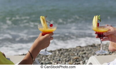 Couple clinking glasses of cocktail on beach in front of sea