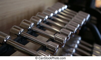 Set of metal dumbbell lying in a row on the stand horizontally