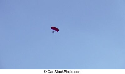 View of skydiver fly in blue cloudless sky Red parachute...