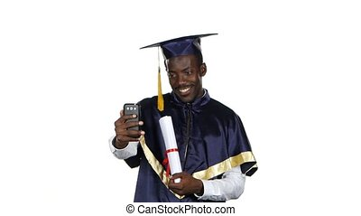 Graduate takes a photo with a diploma. White - Graduate...
