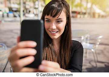 Pretty girl taking selfie - A photo of young woman sitting...