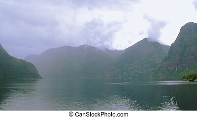 Panoramic view of river at volcanoes covered by green woods...