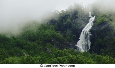 View of cascade waterfall in green forest among volcano. Summer day. Smoke. Nature. Nobody.