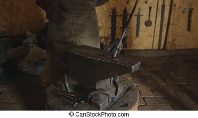 Blacksmith breaks off part of a metal rod with anvil and...