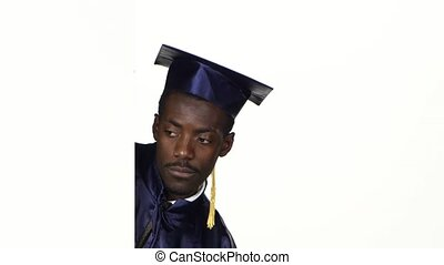Graduate peeks out from behind a corner and shows a finger down. White. Close up
