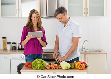 Happy Couple Preparing Food - Wife Helping Her Husband For...