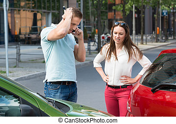 Man On Mobile Phone After Car Collision - Sad Young Man...