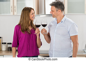 Couple Toasting Red Wine - Portrait Of Happy Couple Toasting...