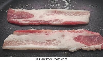 Close up video of two horizontal frying bacon slices clip