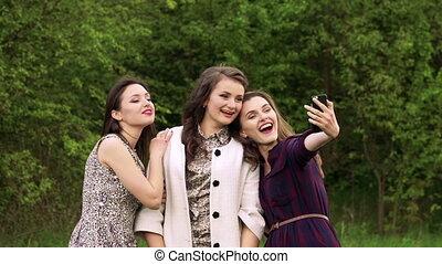 Pretty girls taking selfie in green garden. Slowly