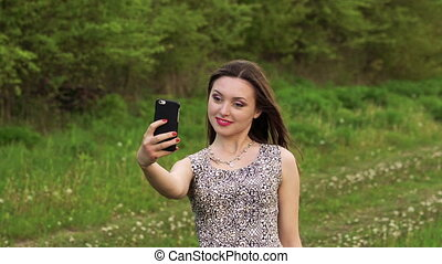 Young girl posing for selfie in the garden. Slowly