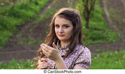 Young model with dandelion in hand looking on a camera. Slowly