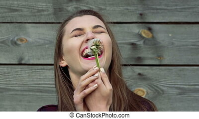 Beautiful young woman blowing dandelion, smiling on wooden background. Slowly