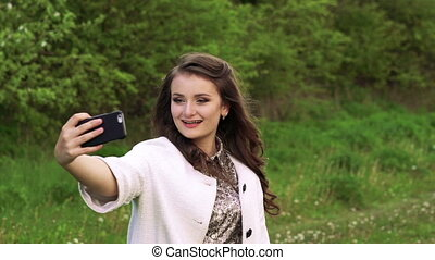 Pretty young girl posing for selfie in the garden. Slowly
