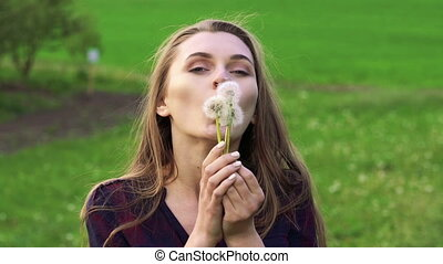 Pretty young woman blowing dandelion and smiling . Slow motion