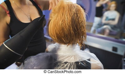 In the professional salon hairstyle on the girl's head dried hairdryer.