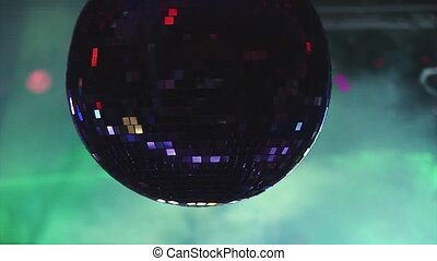 Rotating disco ball reflects sparkling colorful beams from spotlights in nightclub. Smoke. Holidays