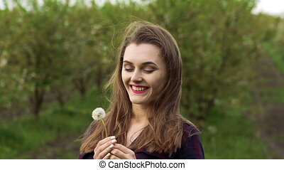 The cute girl blowing the bouquet dandelion in the garden. Slow motion