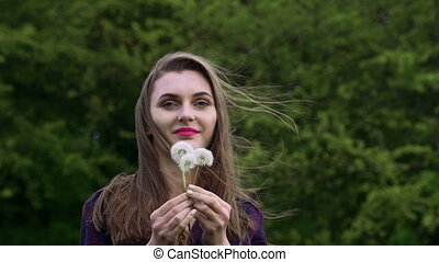Nice girl blowing the bouquet dandelion in the garden. Slow motion