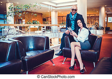 Beautiful couple sits in the hall of the hotel