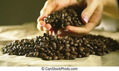 Young woman hands with beautiful nail polish draw some roasted coffee beans