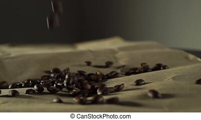 Pouring down coffee beans on brown paper, slow motion video...