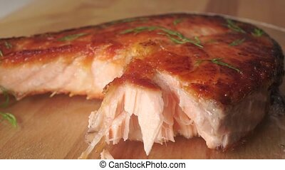 Picking pieces of salmon steak with a fork, close up shot...