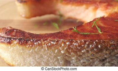 Crispy salmon steak on light wooden cutting board, close up dolly shot