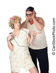 Wife listening to music while husband covers his ears