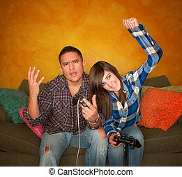 Hispanic Man and Girl Playing Video game - Attractive...