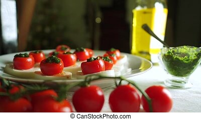 Adding balsamic vinegar to cheese and tomato salad Caprese ....