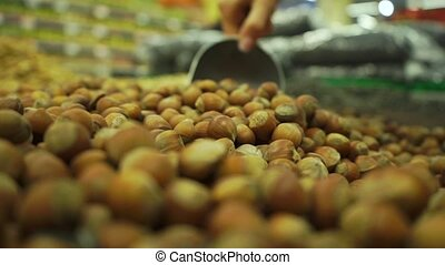 Picking some hazelnuts with a scoop in supermarket clip