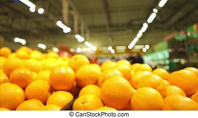 Dolly shot of oranges in big boxes in a food store