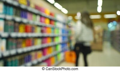 Unrecognizable girl chooses shampoo in supermarket. Bokeh...