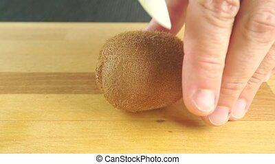 Man hands dividing kiwi with white knife clip