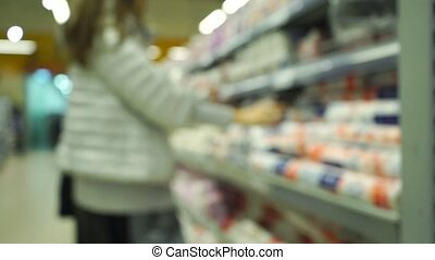 Blurred young woman chooses goods in supermarket. Bokeh slow motion video