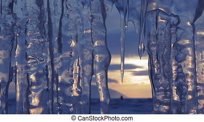 Setting sun is reflected in icicles. Beautiful winter Lake...