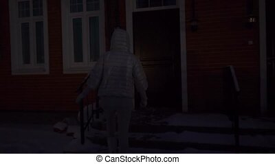 Girl in silver winter jacket entering townhouse at night,...