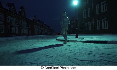 Lonely girl in silver winter jacket walking on snow in...