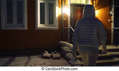 Young woman in winter jacket entering townhouse at night,...