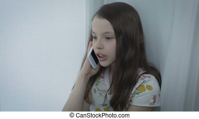Beautiful little girl emotional talking on smart phone -...
